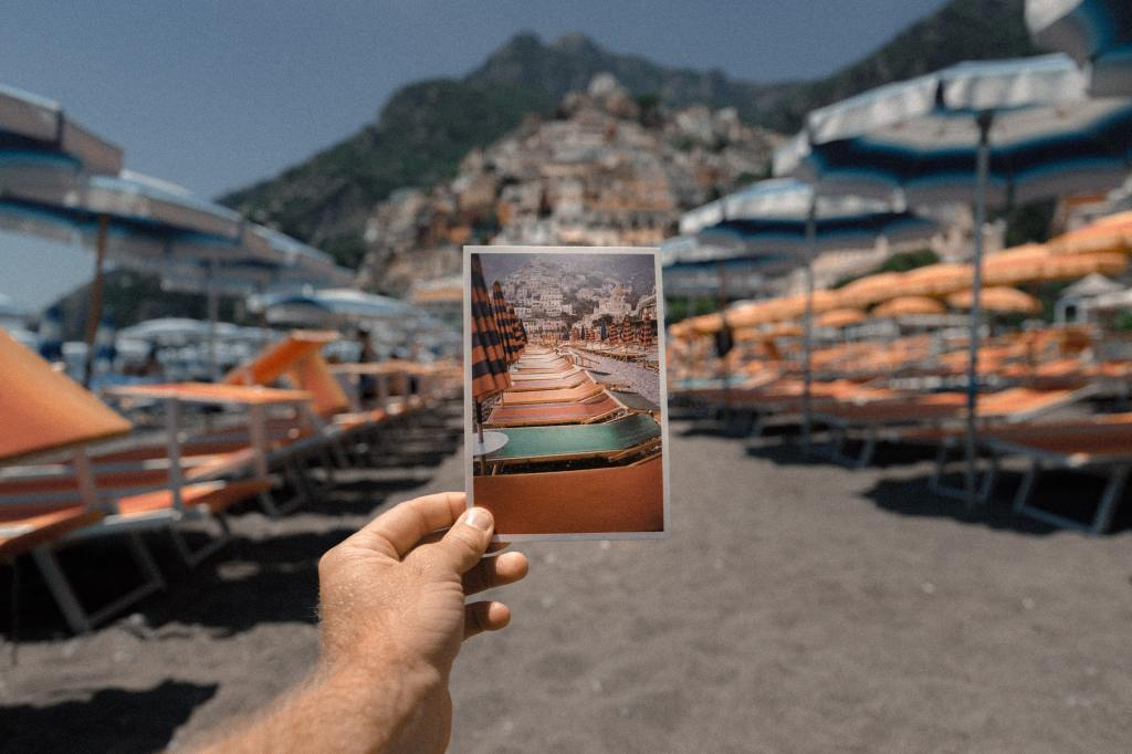 An image of a polaroid being held in front of the beach it was taken on.
